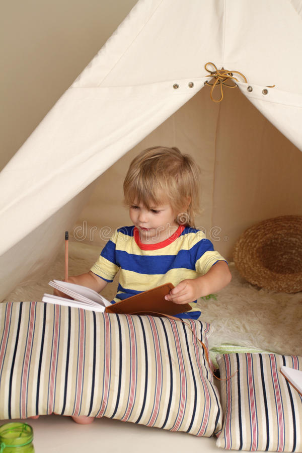 Indoor Play with Teepee Tent. Child playing at home indoors with a teepee tent stock images