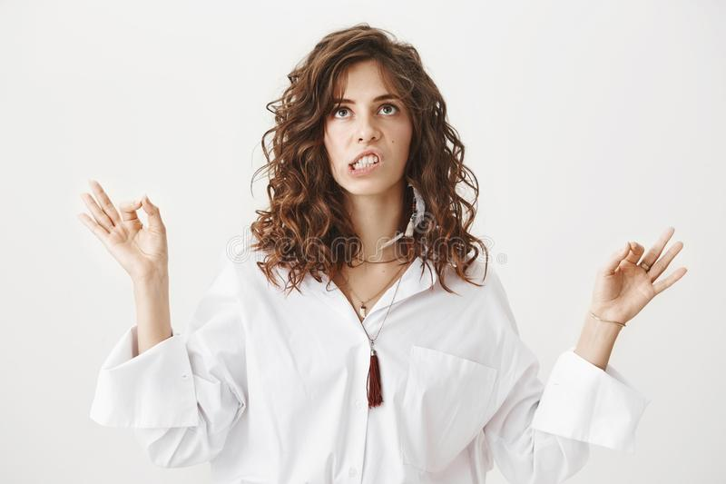 Indoor portrait of annoyed unfocused adult woman trying to meditate, standing with lifted hands and yoga signs with lack. Of concentration, irritated by noise stock images