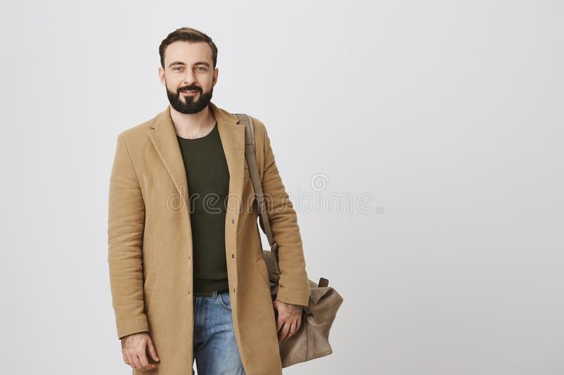 Indoor portrait of attractive businessman in coat and casual clothes, holding bag on shoulder and smiling at camera stock photo