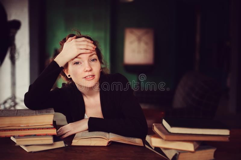 Indoor portrait of beautiful redhead woman learning or reading books in university stock photography