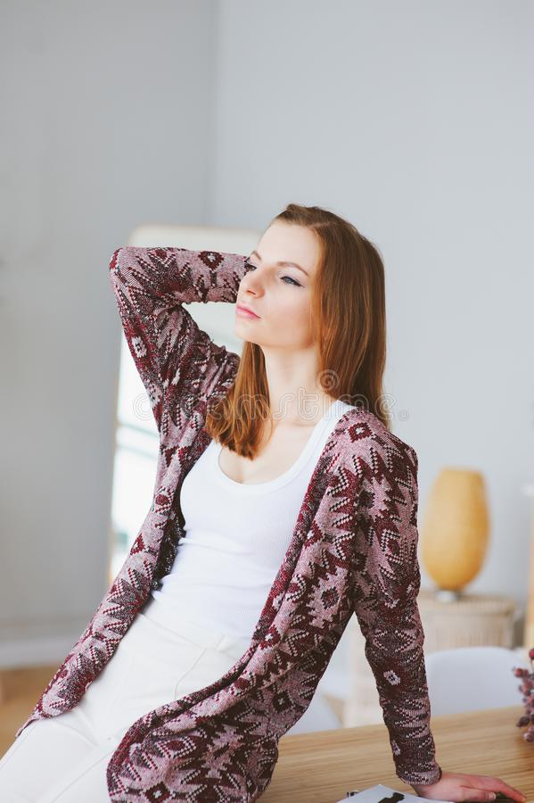 indoor portrait of beautiful young woman posing at home in warm cozy cardigan stock image