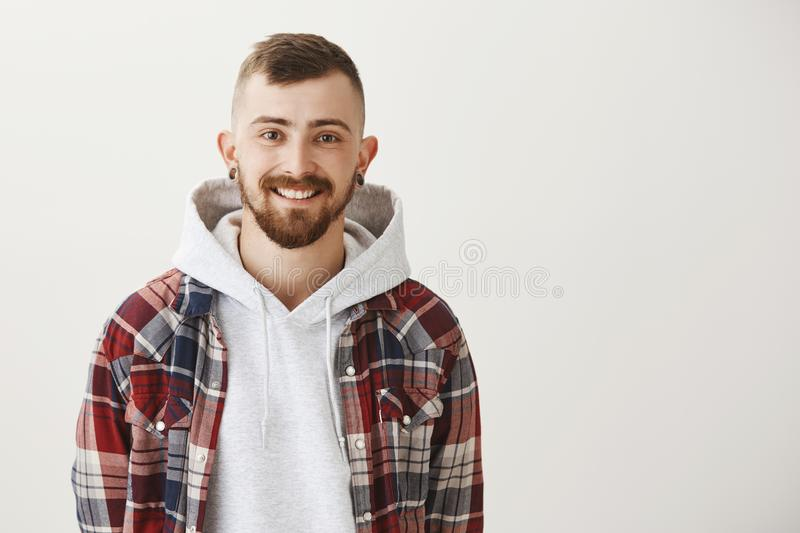 Indoor portrait of carefree joyful male student in plaid shirt over stylish hoodie, smiling cheerfully and gazing at royalty free stock images