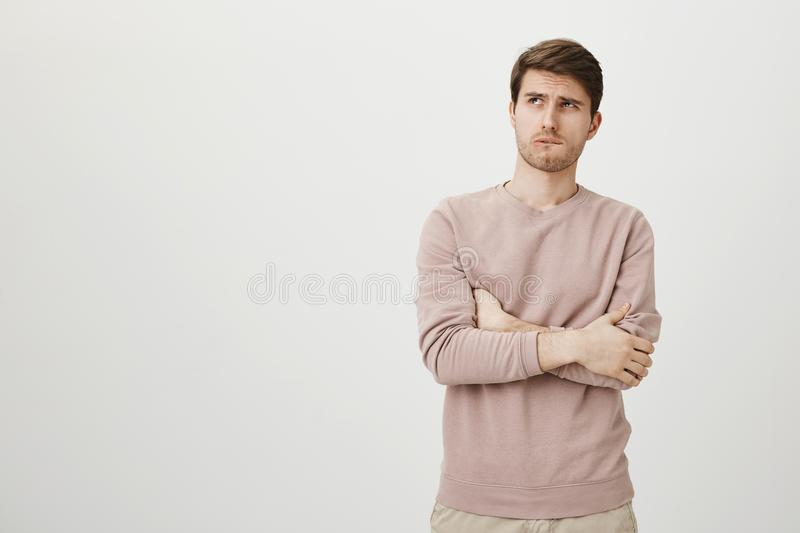 Indoor portrait of charming handsome european guy in formal shirt holding smartphone and smiling cheerfully at camera. Messaging girlfriend while hanging out stock photos