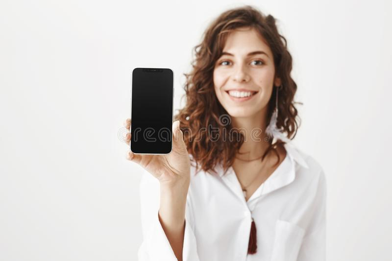 Indoor portrait of charming young woman with curly hair smiling broadly while holding smartphone, advertising gadget. While standing over gray background in royalty free stock photos