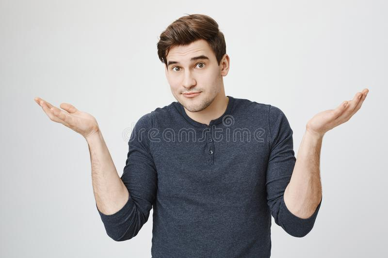 Indoor portrait of confused handsome guy showing I have no idea gesture, shrugging shoulders and raising hands, standing stock photography