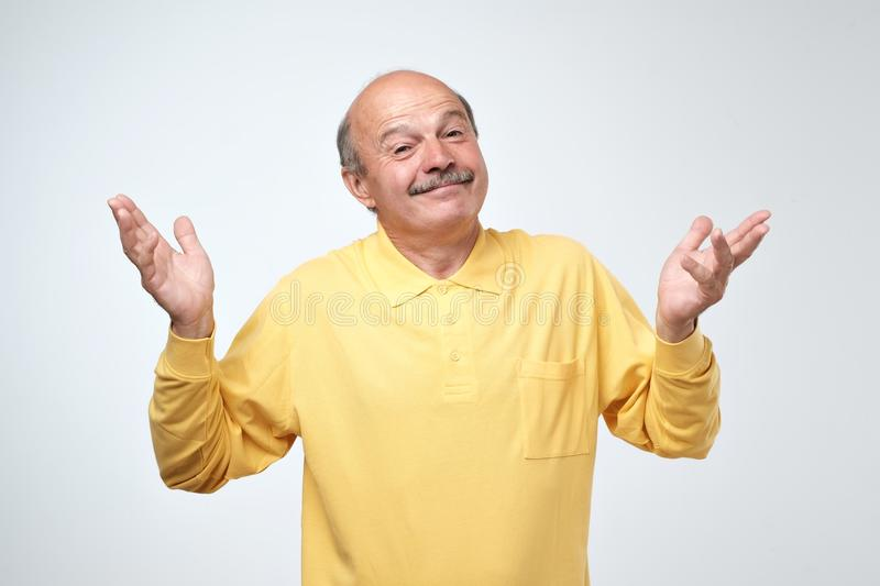Indoor portrait of confused senior man in yellow t-shirt showing I have no idea gesture. Shrugging shoulders and raising hands, standing against gray royalty free stock photo