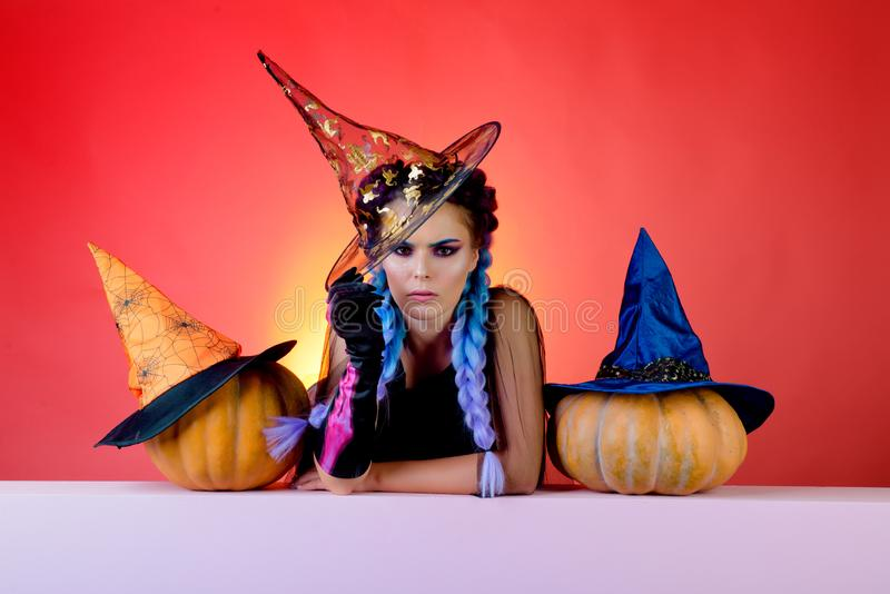 Indoor portrait of cute young witch at halloween party. Halloween Witch with pumpkin. Emotional young woman in halloween royalty free stock images