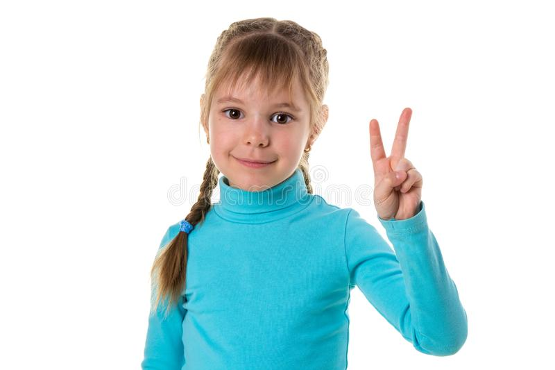 Indoor portrait of European girl isolated on white background with optimistic smile, showing victory sign looking royalty free stock photo