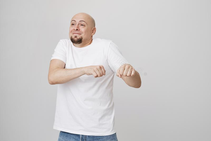 Indoor portrait of funny excited bald caucasian guy making dance move as if celebrating something, being in great mood stock photography