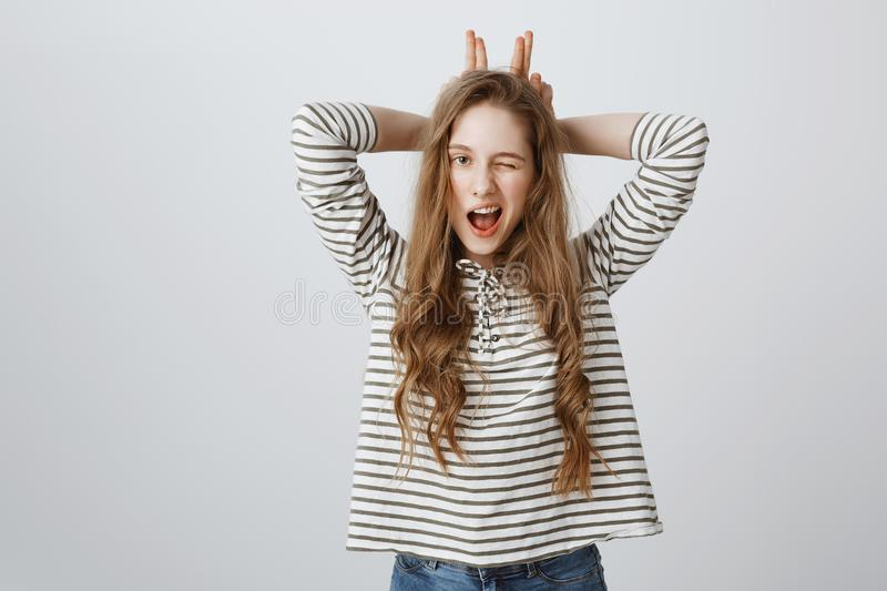 Indoor portrait of good-looking young european woman winking, holding fingers behind head as if mimicking ears, feeling royalty free stock photos