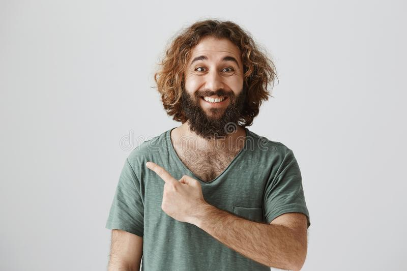 Indoor portrait of handsome kind arabian man with curly hair and beard smiling broadly while pointing left or behind royalty free stock photography