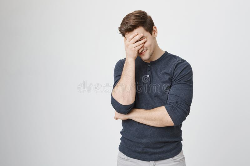 Indoor portrait of handsome man with stylish haircut, wearing casual clothes, making facepalm gesture while smiling royalty free stock photography