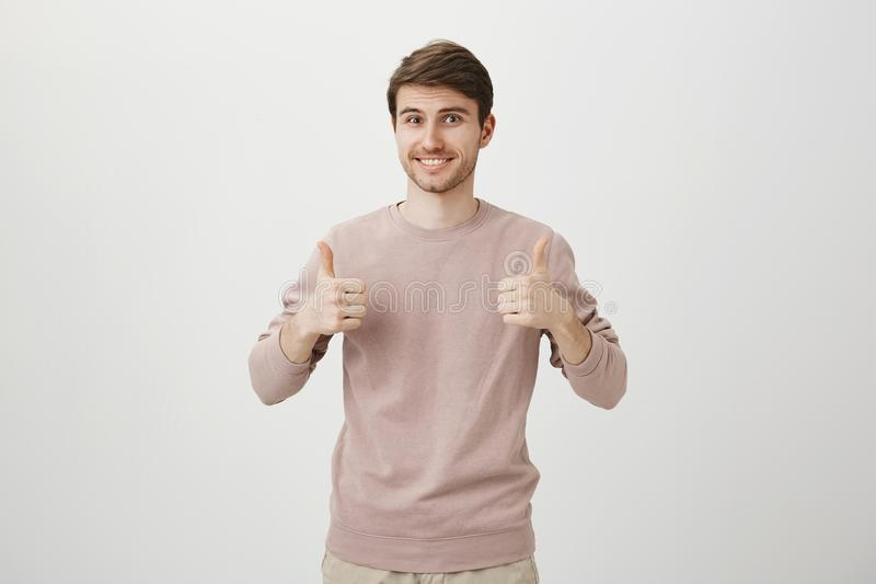 Indoor portrait of happy charming guy giving positive reply with raised thumbs up, smiling broadly and standing against. Gray background. I agree to join your royalty free stock images