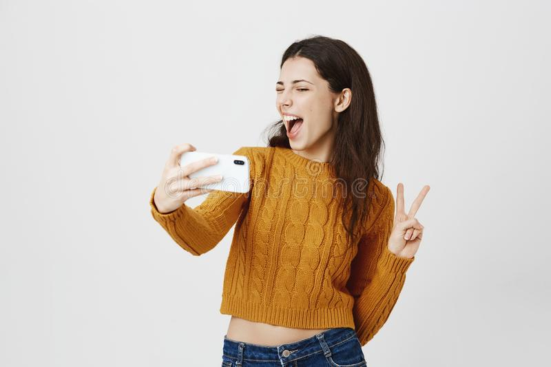 Indoor portrait of happy excited woman taking selfie with victory gesture, winking at smartphone and standing with. Opened mouth over gray background. Trendy stock photos