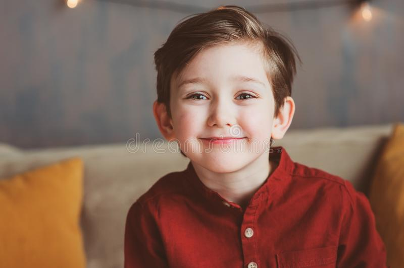 Indoor portrait of happy handsome stylish child boy sitting on cozy couch. In casual clothing stock photography