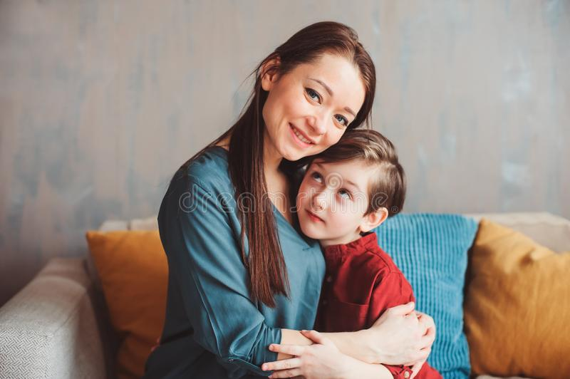 Indoor portrait of happy loving mother comforting toddler son at home. stock photography