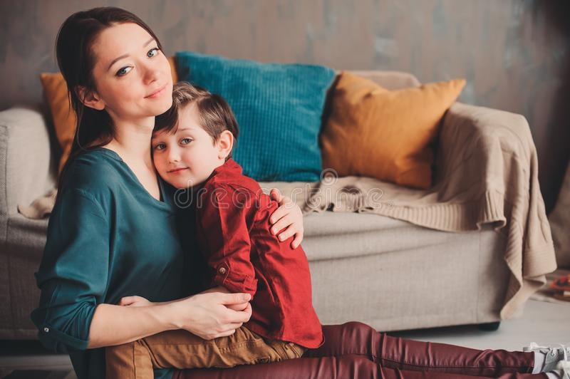 indoor portrait of happy loving mother comforting toddler son at home. stock images