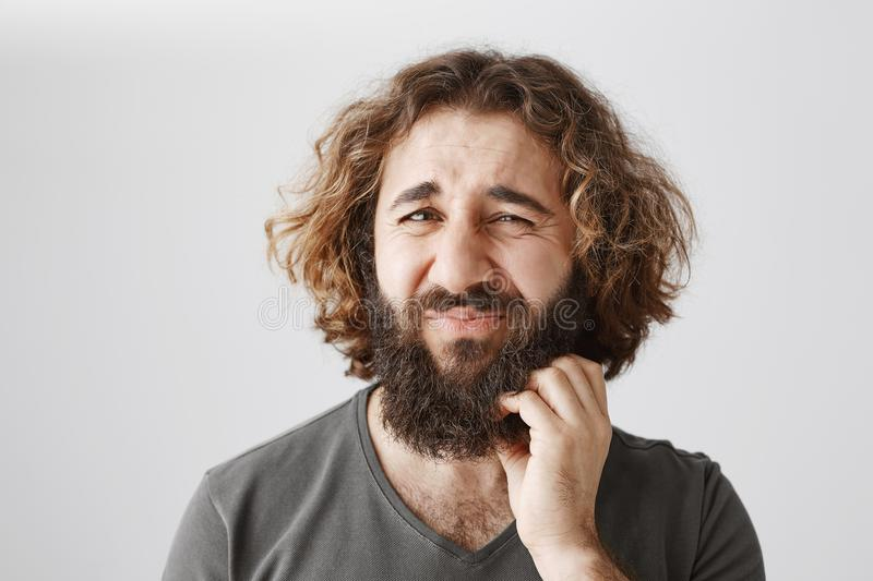 Indoor portrait of hesitating uncertain eastern male with curly hair frowning and scratching beard, expressing royalty free stock photos