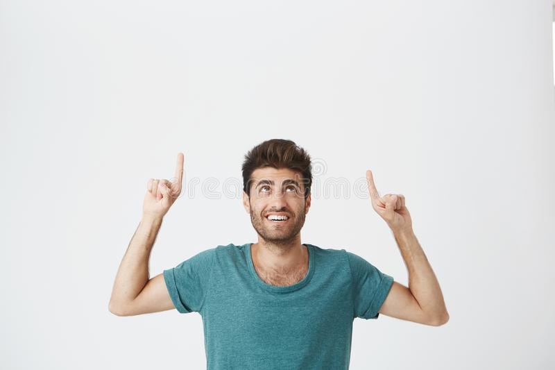 Indoor portrait of joyful bearded spanish guy with pleased expression, wearing blue tshirt, laughing and pointing upside royalty free stock photo