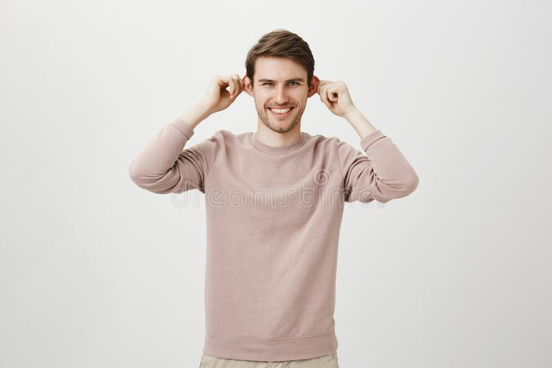 Indoor portrait of joyful good-looking caucasian man stretching ears while smiling and looking like monkey, standing. Against gray background. Handsome guy royalty free stock images