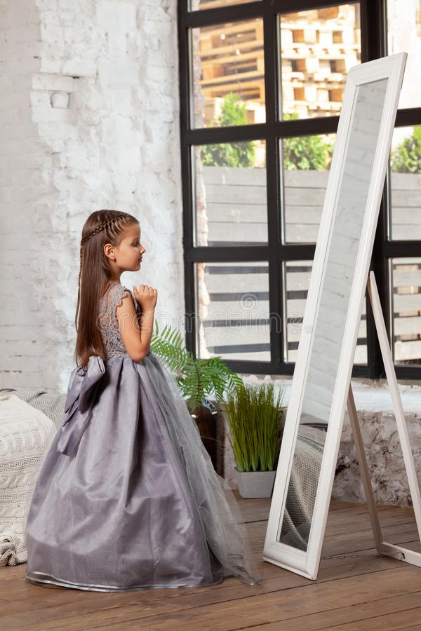 Indoor portrait of a little charming girl wearing in a beautiful dress. stock images
