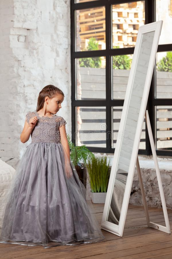 Indoor portrait of a little charming girl wearing in a beautiful dress. stock image