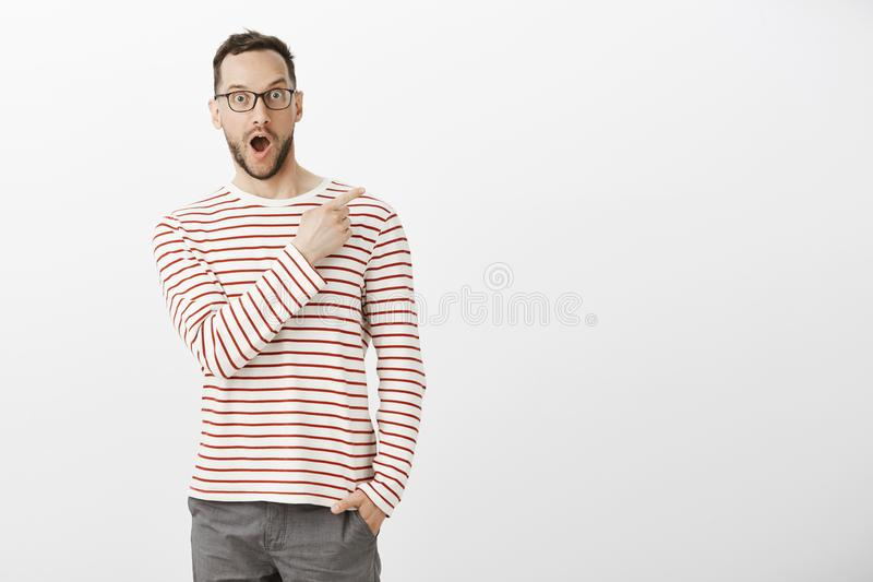 Indoor portrait of pleased impressed handsome man in eyewear, pointing at upper right corner, dropping jaw from positive. Emotions, asking about product royalty free stock photos