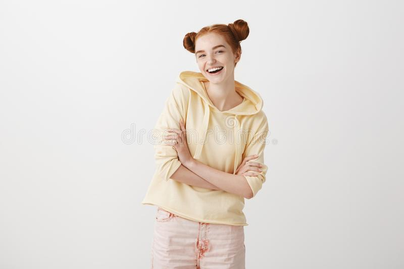 Indoor portrait of positive happy redhead teenager with trendy two buns hairstyle, holding crossed hands on chest and stock photo