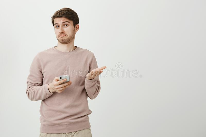 Indoor portrait of puzzled and clueless young man gesturing and shrugging while holding smartphone and looking confused. At camera. Strange, I thought I saved royalty free stock photography