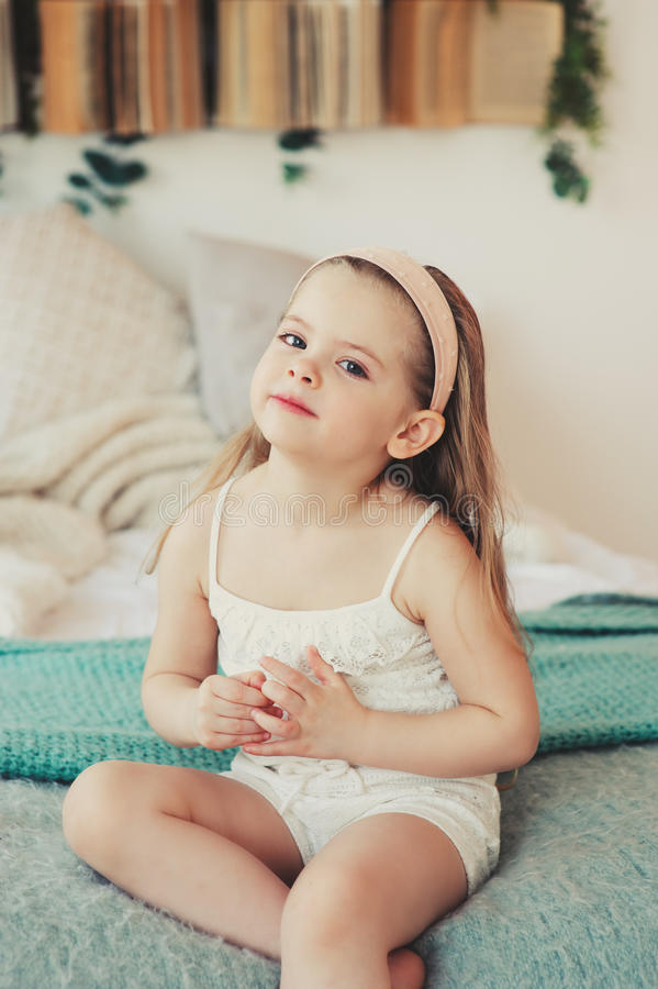 Indoor portrait of sad 5 years old child girl. Sitting on bed royalty free stock image