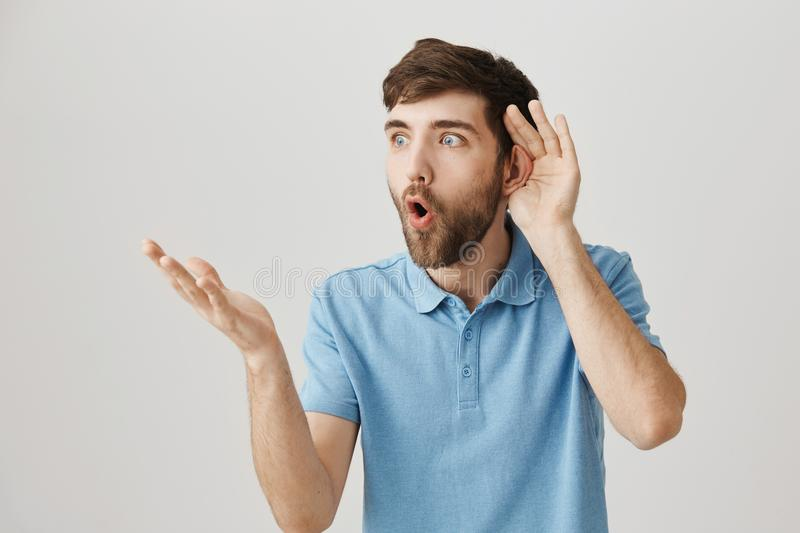 Indoor portrait of shocked and impressed guy holding hand near ear while overhearing gossip and gesturing as if he can royalty free stock image