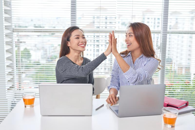 Indoor portrait of smiling girls working together in office stock image