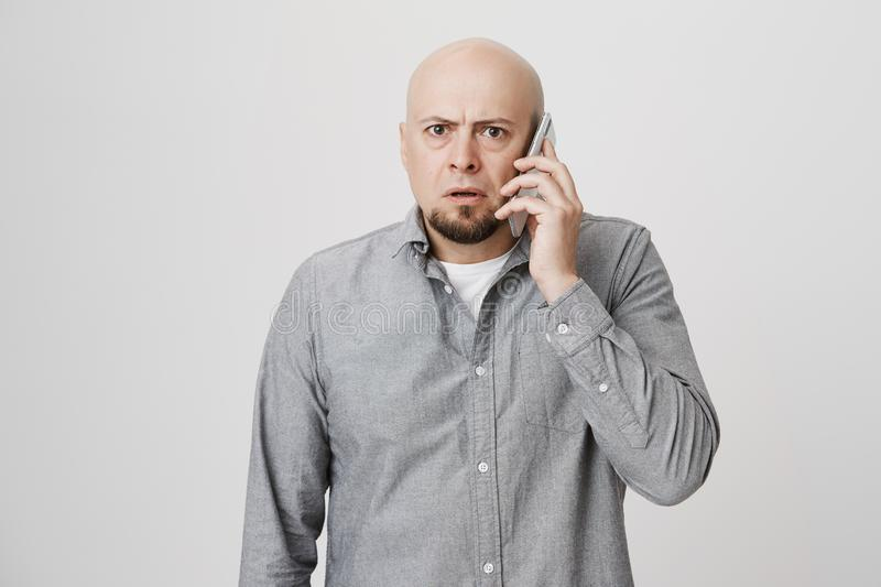 Indoor portrait of worried and confused bald man with beard, talking on phone and being shocked with what he hears royalty free stock image