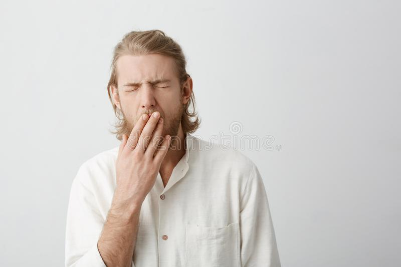Indoor portrait of young attractive blond male yawning and covering mouth with hands, standing with closed eyes over royalty free stock images