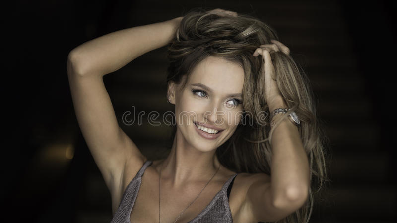 Indoor portrait of a young beautiful fashionable woman wearing stylish accessories. Hidden eyes with hat. Female fashion stock photos