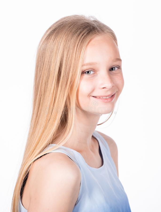 Indoor profile portrait of charming caucasian fair-haired young girl in trendy blue blouse, smiling broadly and feeling stock photography