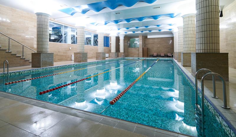 Indoor public swimming pool interior in fitness gym club. Healthy concept stock photography
