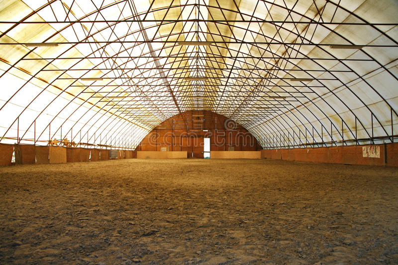 Indoor riding arena covering sand for trainings. Indoor riding hall and equestrian center for trainings and events stock photos