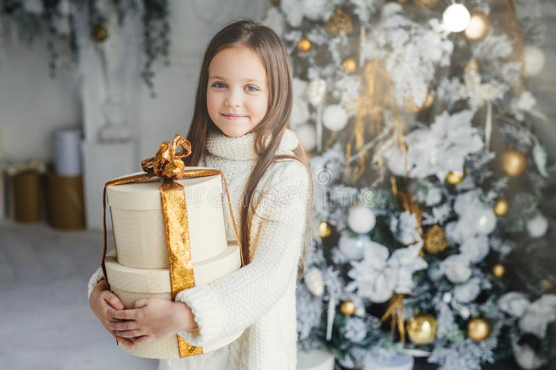 Indoor shot of adorable cute pretty small female child wears warm knitted clothes, holds huge wrapped present gift, recieves from royalty free stock images