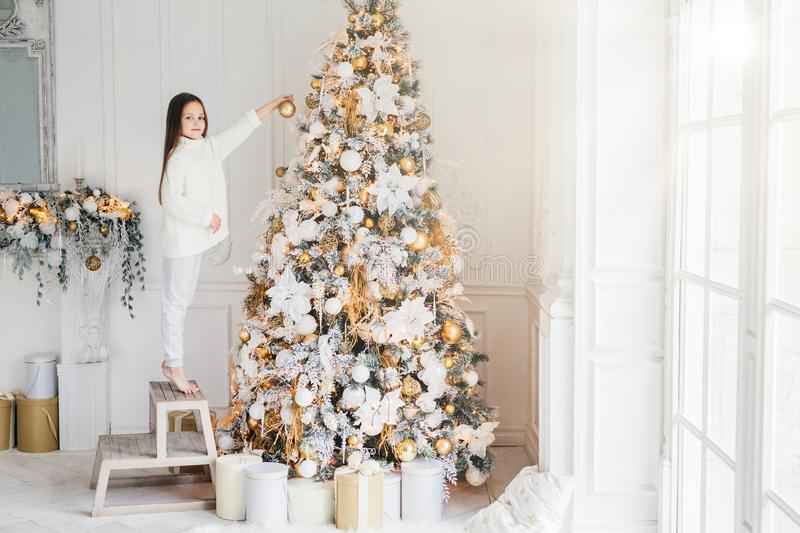 Indoor shot of adorable little kid stands on chair on tiptoes, decorates big New Year tree, has good mood, being in anticipation o. F holidays and wants to stock photos