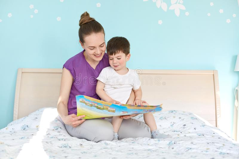 Indoor shot of affectionate woman and small boy read interesting story from book, sit at bed, enjoy calm atmosphere, smile stock image