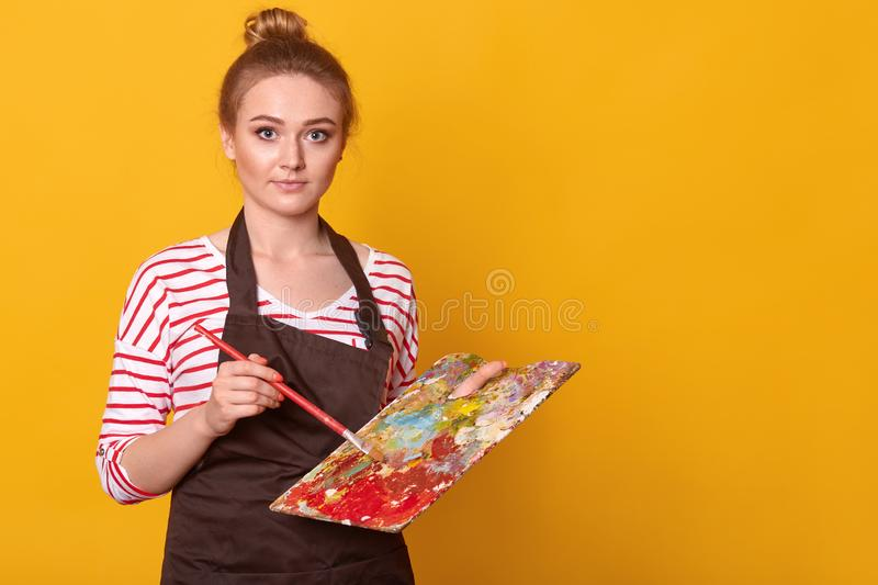 Indoor shot of attractive blue eyed young painter standing isolated over yellow background in studio, mixing colors at dirty stock image