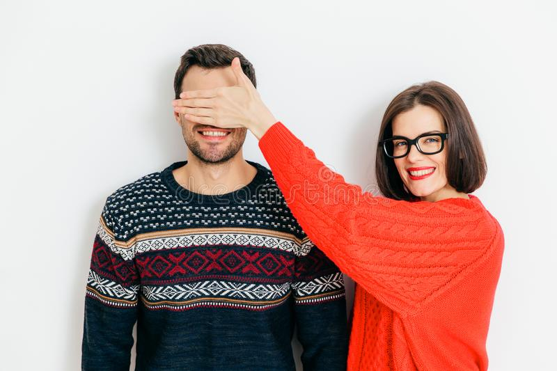 Indoor shot of attractive brunette female with positive expression, covers man`s eyes, wear winter sweaters, stand together again royalty free stock images