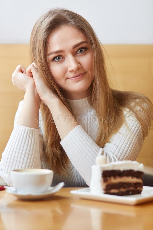 Indoor shot of attractive freckled blonde female spends day off in cafeteria, drinks coffee and eats tasty cake, looks directly at. Camera, enjoys spare time royalty free stock photo