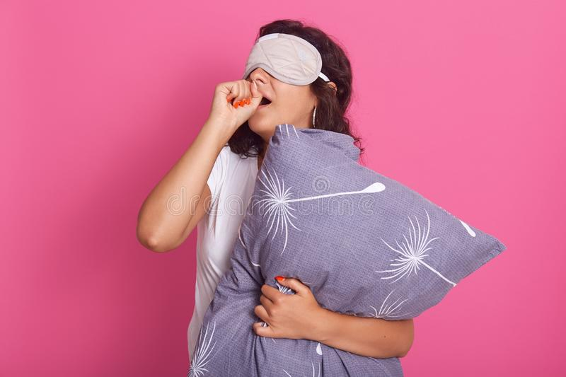Indoor shot of attractive young woman standing against pink studio wall, posing in sleeping mask on her eyes and pajamas, holding. Pillow, covering mouths with stock images
