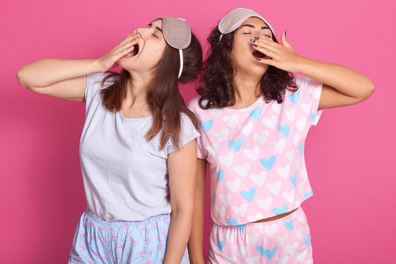 Indoor shot of attractive young women standing against pink studio wall, having fun together, posing in sleeping mask and pajamas stock photos