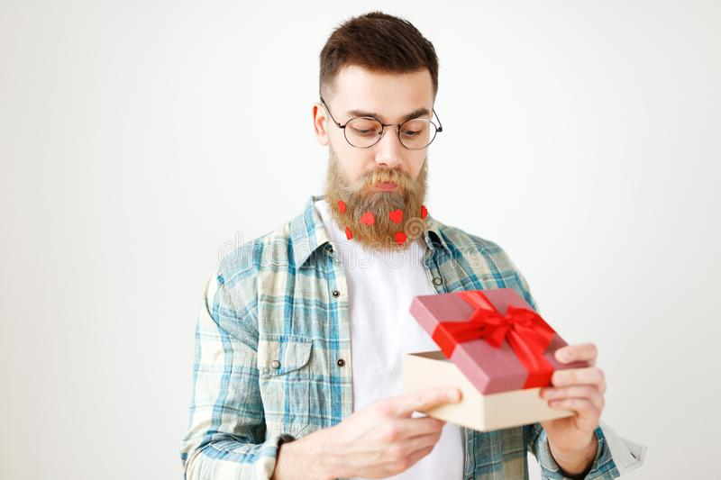 Indoor shot of bearded male model with long thick beard dressed in checkered shirt, opens present box, recieves surprise stock images