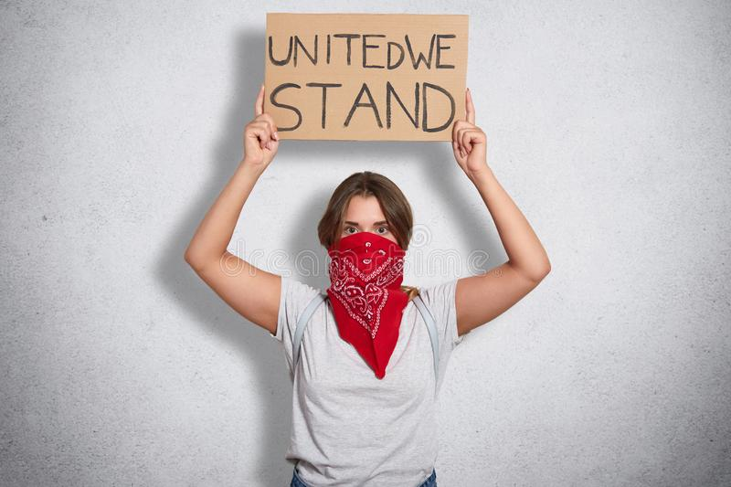 Indoor shot of brave feminist woman raising sign with inscription united we stand, calling for unity, wearing white casual t shirt. And red bandana covering stock photography