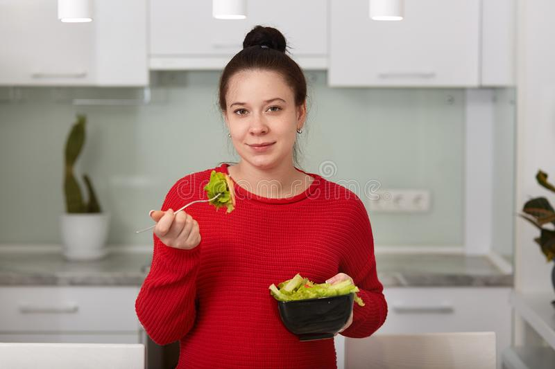 Indoor shot of brunette woman with hairstyle bun, eats delicious vegetarian salad from bowl, wearing red casual sweater, posing stock photography