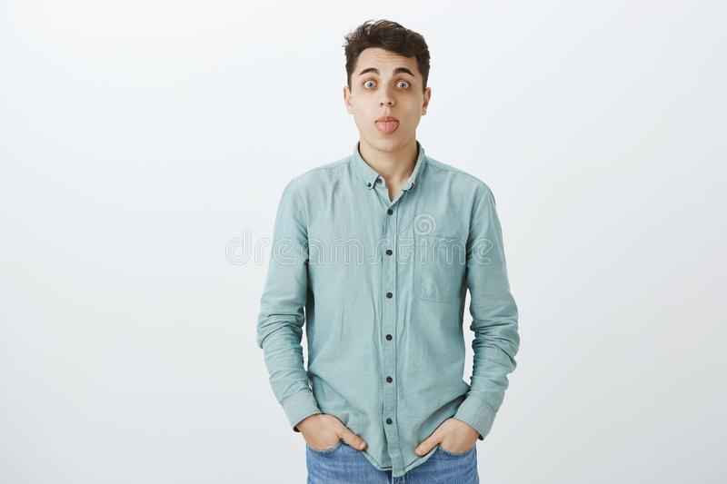 Indoor shot of carefree funny caucasian male in turquois casual shirt, holding hands in pockets, staring at camera and stock photo